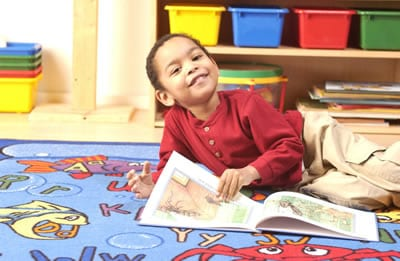 Special Needs child reading a book at home.